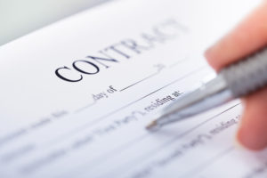 Close up of hand holding pen to prepare and review title insurance contract