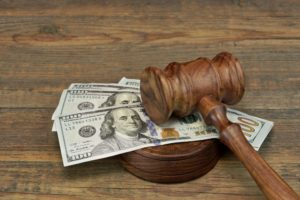 Wooden gavel on top of 100 dollar bills for mechanics lien compensation