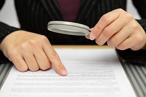 Title Insurance Underwriter closely looking for clerical errors