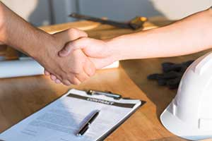people shaking hands over title insurance paperwork for new home construction