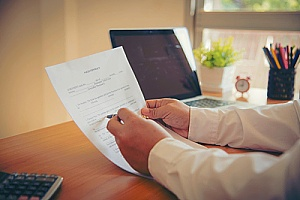a real estate attorney signing paperwork during the home closing process