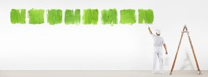 Man painting green nature accents on wall