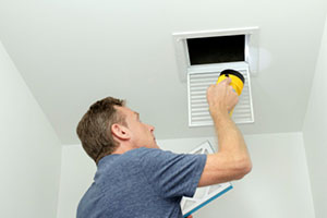 Man looking at air ducts