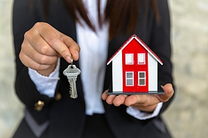 Key to home and small home being held