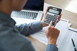 man working on calculator to find a refinanced mortgage