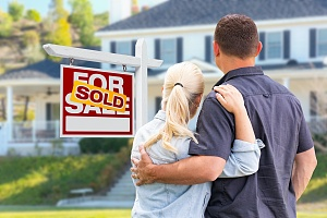 couple standing outside their home that is sold