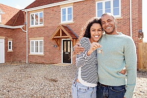 a couple holding keys to new house after finding out what is a Purchase Agreement