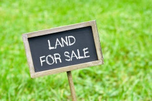 land for sale sign on green grass