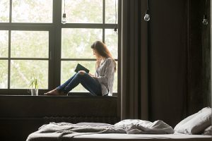 A woman sitting by the window. Refinancing a home is a decision that's most ideal in certain situations
