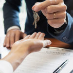 homebuyer is handed key to house after proving commitment of buying home by signing title insurance contract