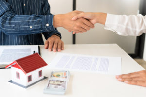realtor and homebuyer shake hands after homebuyer exudes commitment to buy title insurance