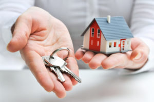 realtor gives homebuyer keys to the house after homebuyer showed commitment to buy house by paying down payment of house and title insurance policy