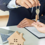 realtor hands key to homebuyer after resolving private mortgage insurance isuue
