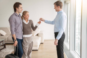 realtor hands key to homebuyers after they bought home and title insurance signifying their commitment