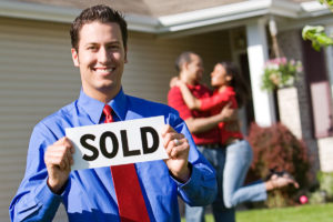 realtor holds sold sign after selling title insurance policy and helping couple reach their commitment to buy a house