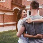 couple with their new home after learning title insurance terms