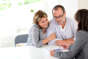 broker explains the refinancing options to the couple
