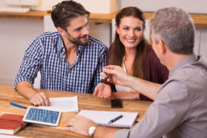 broker hands key to homeowners after they paid the down payment and owners title insurance policy of their home