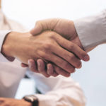 client shakes broker hand before they talk about title insurance