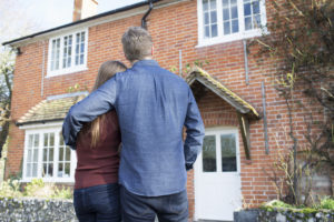 couple stand in front of their new home after settling owners title insurance dispute
