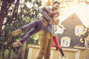 father plays with his daughters after securing owner's title insurance for the house