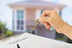 homeowner is handed key to home after signing owner's title insurance policy contract