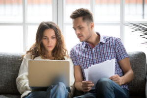 homeowners use laptop to find useful information regarding their title insurance policy