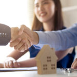insurance broker shakes homeowner hand before talking about the owner's title insurance policy