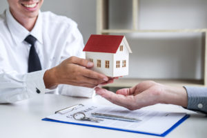 realtor gives miniature house to homeowner after he signs title insurance policy contract