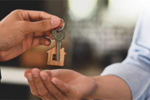 realtor hands house key to homeowner after the homeowner bought a title insurance policy