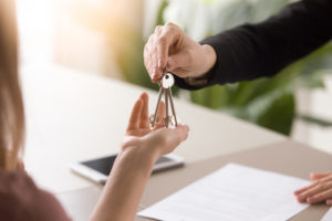 broker hands keys to new homeowner after homeowner signed the owners title insurance contract