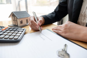 calculator sits on top of the document the mortgage broker is signing
