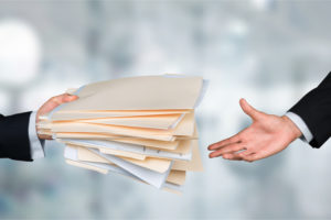 employee gives the title underwriting folders to colleague