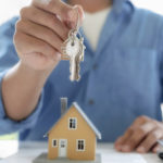 insurance broker hands the new homeowner the keys to house after the homeowner signed the owners title insurance policy