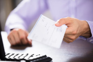lender's title insurance compensation check is handed to a policyholder