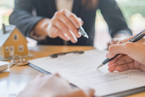 mortgage broker explains the contract as the homebuyer signs the document