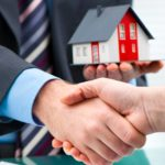 mortgage broker shakes new homeowner hand after homeowner sign the owner's policy