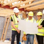 the builders look at the blueprint after attaining owner's title insurance for the under construction building