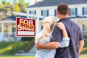 the first time home buyers stand in front of their home