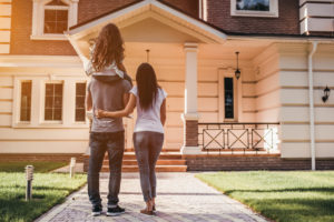 the homeowners stand in front of their new home after acquiring an owners title insurance policy