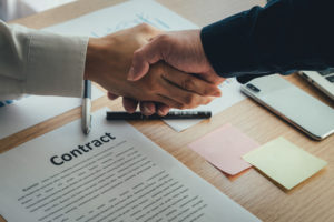 the two parties shake hands after coming to an agreement regarding the title insurance contract