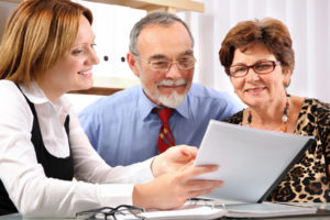 employee of a title settlement services firm shows document to new homebuyers