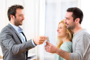 title company employee hands the house key to the new owners