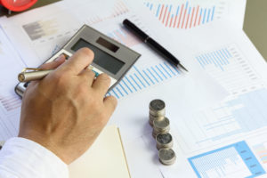 title company employee makes calculations next to coins stacked on some documents