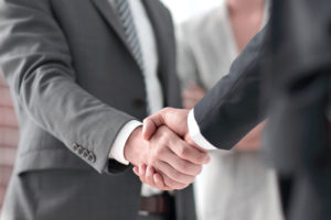 title company employee shakes a clients hand before their meeting