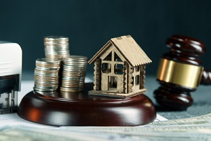 row of coins on a small house model and a law auction hammer for mechanic's lien
