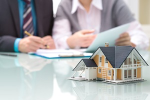 businessman signs contract behind home architectural model knowing What Does Title Insurance Not Cover