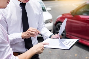 insurance agent writing on clipboard while examining car for lenders title insurance