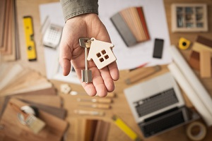 real estate agent handing over a house key with Owner's Title Insurance