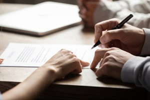 solicitor pointing at insurance contract showing male client